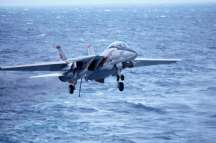 a military jet fighter, f-14, lands on the uss kitty hawk